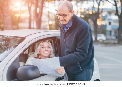 Middle-aged beautiful woman asking the way from passerby - Old man showing the place on the map - travelling, transportation and reason for dating concept