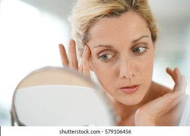 Middle-aged blond woman applying anti-aging cream in front of mirror
