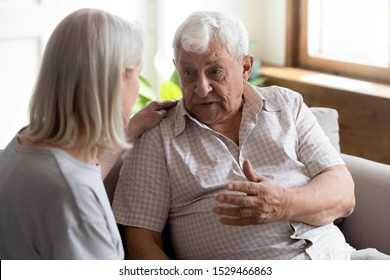 Middle-aged blond woman put hand on 70s man shoulder attentive listens him and showing care and support while old male share problems telling about life to geriatric nurse, concept of nursing services