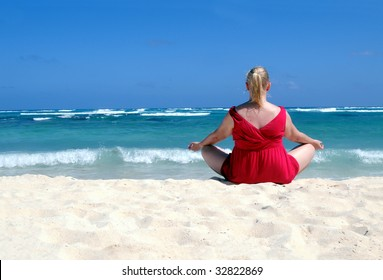 Middle-aged blond woman in red meditating on tropical beach with turquoise water, waves hitting in the white sand