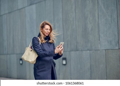 Middle-aged blond woman walking in the wind down an urban street alongside a grey wall with her hair blowing in the breeze reading a text message on her mobile phone