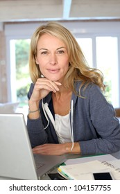 Middle-aged blond woman working at home with laptop