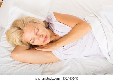 Middle-aged blonde female sleeping on white pillow in bed at home