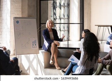 Middle-aged blonde woman business trainer teaches group of young specialists gathered together in modern workspace office room listening experienced coach mentor explain lecture topic using flip chart