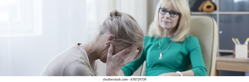 Middle-aged blonde woman crying during psychotherapy in office
