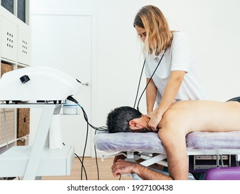 middle-aged, blond-haired female physiotherapist massages the back of a patient who is lying face down on the clinic's stretcher. Osteopathic treatment. Health concept