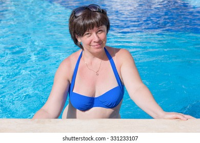 middle-aged brunette on a sun lounger by the pool
