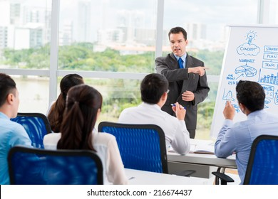 Middle-aged businessman conducting seminar for his colleagues