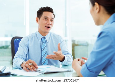 Middle-aged businessman discussing document with his female employee