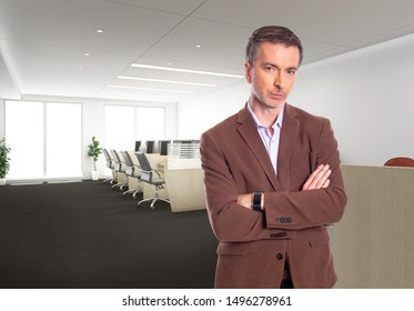 Middle-Aged businessman with gray hair and wearing a brown jacket standing in an office.  Depicts startup and corporate business.  He is looking confident or arrogant.