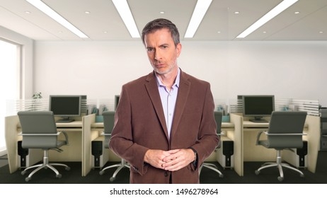 Middle-Aged businessman with gray hair and wearing a brown jacket standing in an office.  Depicts startup and corporate business.  He is looking upset or angry.