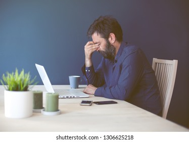 Middle-aged businessman having head ache during work at home office