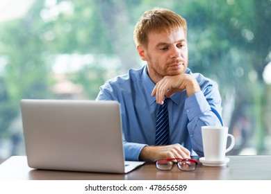 Middle-aged businessman sitting at desk with laptop and having break