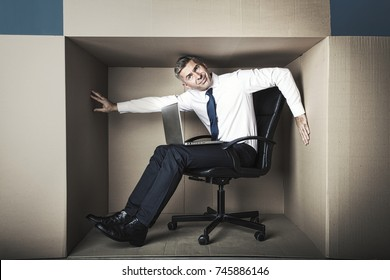 middle-aged businessman in small office box working on laptop, he needs more space