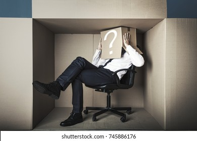 middle-aged businessman in small office box in an uncomfortable position he has a cardboard box with a question mark on his head