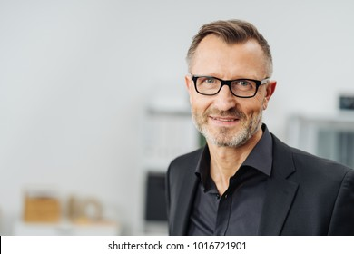 Middle-aged businessman wearing glasses smiling at the camera in a head and shoulders portrait with copy space
