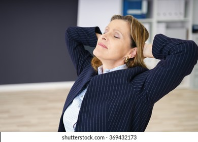 Middle-aged businesswoman de-stressing at work in the office sitting back with her eyes closed and a serene expression