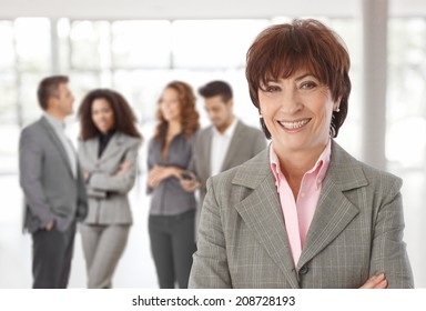 Middle-aged businesswoman in front, business team talking in background.