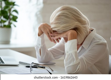 Middle-aged businesswoman took off eyeglasses lowered head over workplace desk feels unhealthy having migraine head ache caused by workload, dismissed senior employee crying age discrimination concept