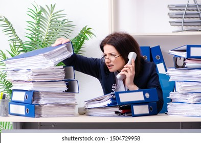 Middle-aged businesswoman unhappy with excessive work