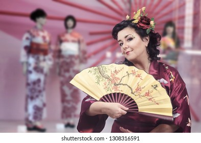 Middle-aged Caucasian brunette woman in kimono and rose in the hair stretches the fan showing its design of blooming sakura on the blurred storefront background.