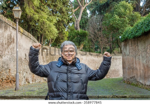 Middle-aged Caucasian man with gray hair dressed in black down jacket rejoices with his arms up holding a brochure in his hand in a street of ancient Rome