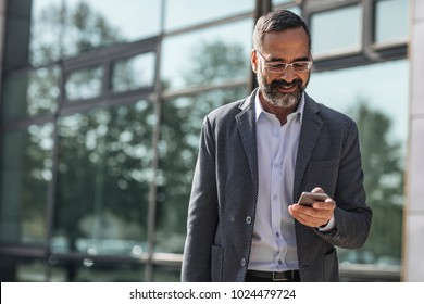 Middle-aged Caucasian smiling businessman standing outdoors and reading on his cell phone.