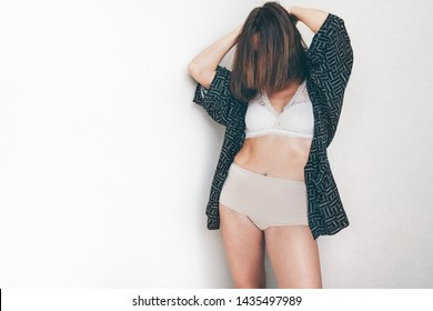 Middle-aged Caucasian woman in light tones bra and panties underwear posing near light background wall.  Natural genuine imperfect female body beauty broking stereotypes concept image.