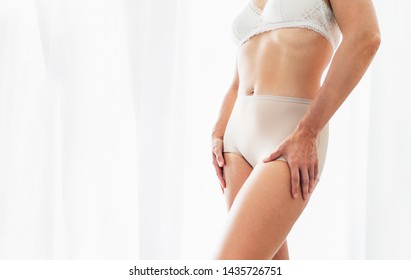 Middle-aged Caucasian woman in light tones bra and panties underwear posing near bright sunny backlight window background.Natural genuine imperfect female body beauty broking stereotypes concept image