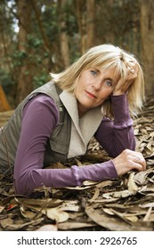 Middle-aged Caucasian woman lying on ground in forest.