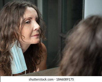 Middle-aged caucasian woman suffering with acne on her chin after wearing protective face mask. Looking at mirror.