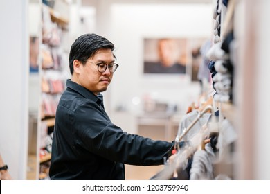 A middle-aged Chinese man is shopping for clothing and apparel for himself in a fast fashion store. He is browsing through the shelves and stacks in the clothing store.