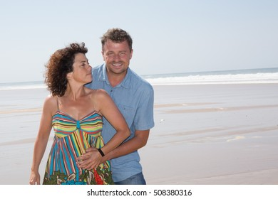 Middle-aged couple at the beach having fun