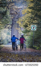 middle-aged couple crossing bridge on bicycle trail