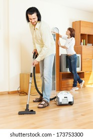 middle-aged couple doing housework together in home