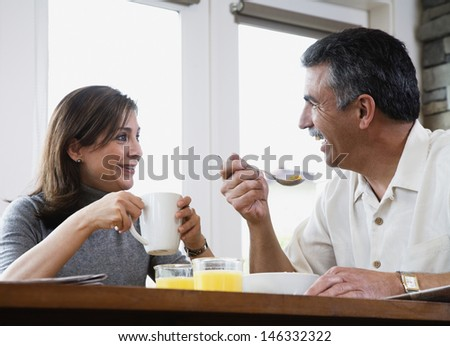 Middle-aged couple eating breakfast