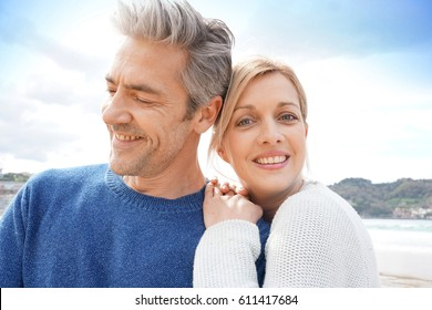 Middle-aged couple embracing each other at the beach