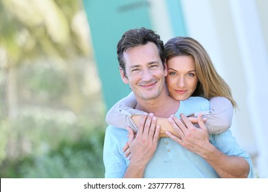 Middle-aged couple embracing in front of house