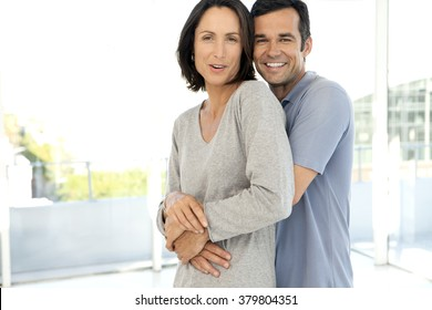 Middle-aged couple hugging in new apartment