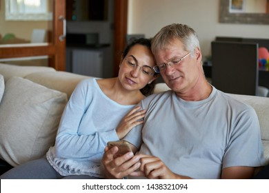 Middle-aged couple looking a mobile phone