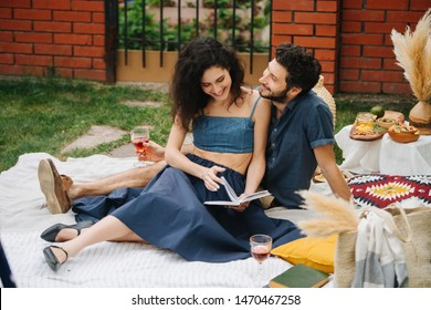 Middle-aged couple in love, drinking rose wine, having a picnic on the lawn in their courtyard, behind a brick fence. They are sitting on a white tablecloth, reading a book together.
