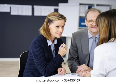 Middle-aged couple in a meeting with a female agent or broker listening attentively to her with a smile, over the shoulder view