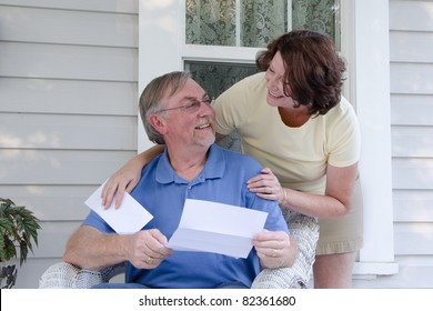A middle-aged couple on an old-fashioned porch look at each other while reading a letter or announcement.