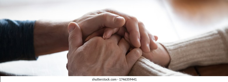 Middle-aged couple sit indoors holding hands close up photo. Spouses feeling connection and love, share problems express empathy showing compassion concept. Horizontal banner for website header design