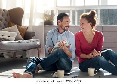Middle-aged couple sitting on floor near window