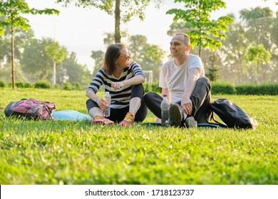 Middle-aged couple sitting on yoga mat, man and woman talking relaxing drinking water. Active healthy lifestyle, relationship, sport, fitness in mature people