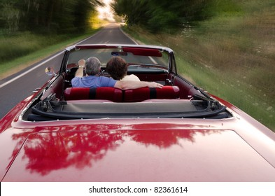 A middle-aged couple snuggle together as they zoom down a county road in a classic red convertible, perhaps on a Sunday drive as they enjoy the experience and each others company.
