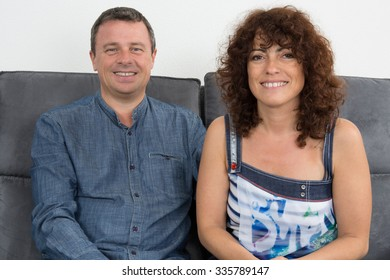 Middle-aged couple in sofa looking at the camera