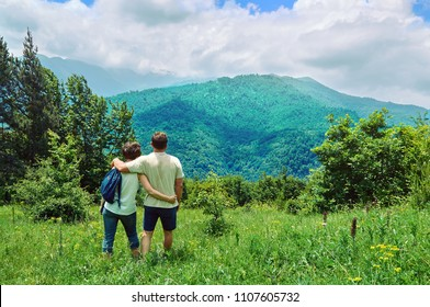Middle-aged couple standing embraced on a green meadow and enjoying breathtaking view in the mountains of Armenia