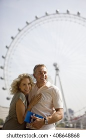 A middle-aged couple standing in front of the London Eye